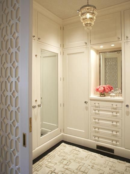 Glamorous closet with ivory rug, ivory cabinets and drawers, vintage crystal chandelier and mirrored doors.