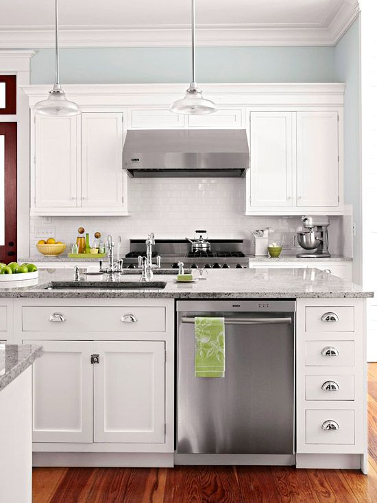 White cupboards, subway tile back splash, stainless steel, grey counters. Clean, contemporary cottage look.