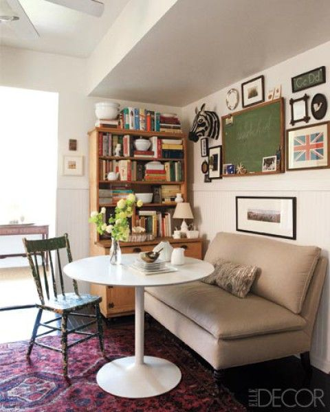 Clever tricks here - armless sofa (takes up so much less actual and visual space), same for table and wooden chair, lots of decorative stuff on the walls, and good storage.  bravo!