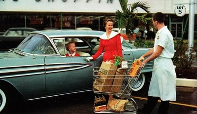 A bag boy helping a woman bring her groceries out to her car. #vintage #1950s #homemaker #grocery_store