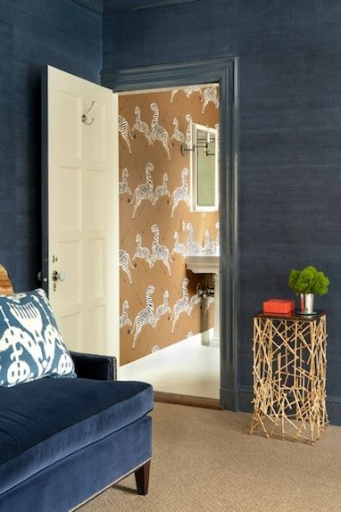 room covered in ink-colored grasscloth; hallway in Scalamandre's gold zebra wallpaper