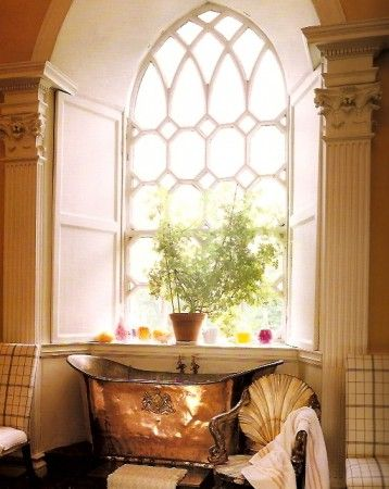 added elegance with this gothic arched window set above an antique copper tub.