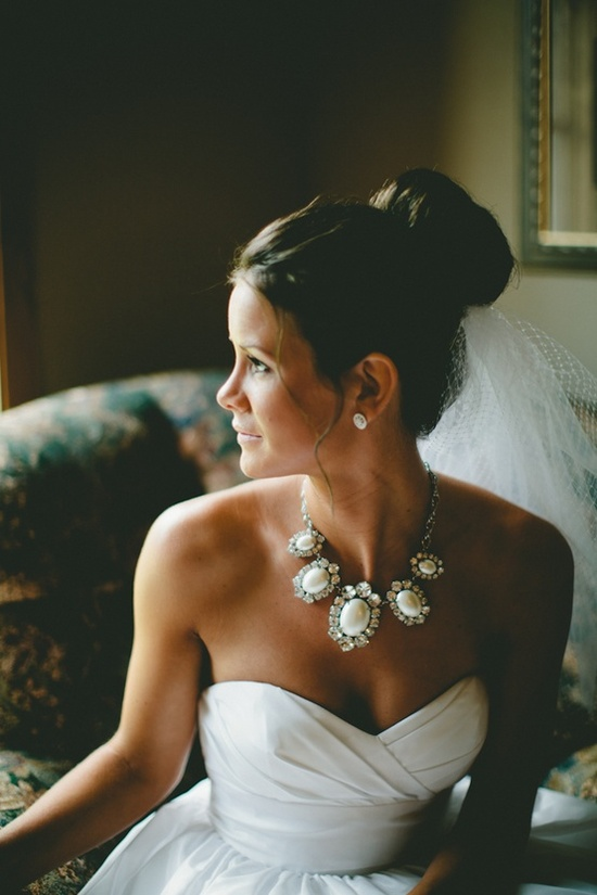 bold statement necklace with a high bun.