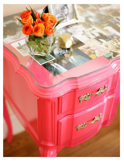 photos under glass top. pink table.