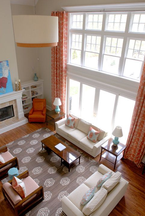 Windows, space, and arrangement of furniture--I really love this tangerine/orangeish color this season and the blue shades that go so well with them. Spectacular room!