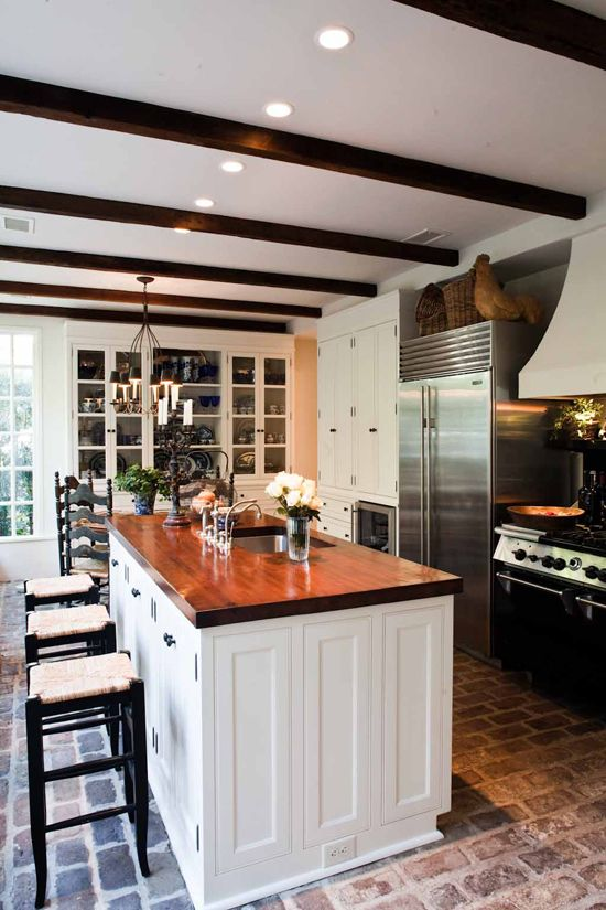 brick floors are what i notice first, warm wood countertop, stained beams, iron chandelier with black shades, beautiful white cabinets with black hardware, glass front built in china cabinet, black painted stools with rush seats - timeless kitchen