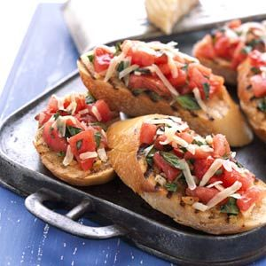 French bread slices are topped with garlic butter and a fresh tomato-basil topper for this grilled appetizer.