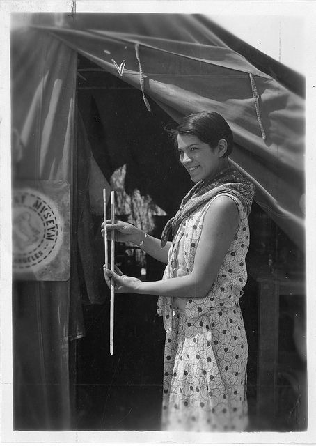 "Bertha Parker Pallan [Cody] (1907-1978) is considered one of the first female Native American archaeologists. The caption to this photograph said that Bertha Pallan was an ""expedition secretary"" who was demonstrating ""the difference in size of early type [small] and large type atlatl darts from Gypsum Cave.""  In 1936, Bertha married Iron Eyes Cody (1904-1999). In the 1950s, they hosted a television program explaining Indian history and folklore and served as technical advisers on several films."