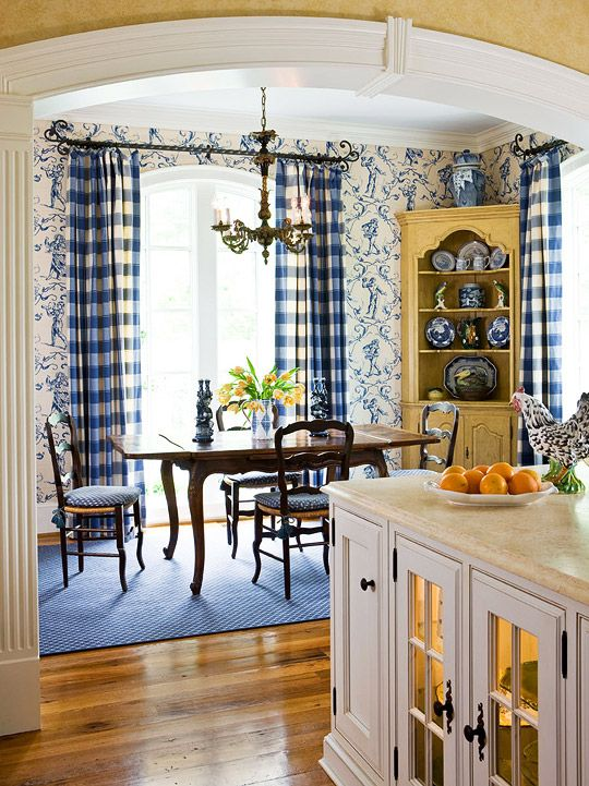 The kitchen breakfast area is casually classic, with walls covered in blue-and-white toile. Buffalo plaid at the windows frames the streams of sunlight that pour through the glass. Around the table, chairs are cushioned with a playful material in blue. A painted yellow corner cabinet houses Wanda's collection of blue-and-white ceramics.