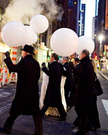 Guests walk down Fifth Avenue with balloons on their way to the reception