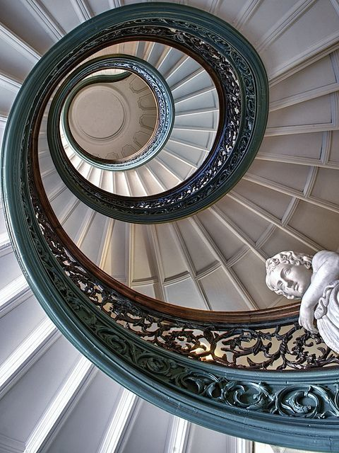Swirling spiral staircase with teal wrought iron banister. George Peabody Library in Maryland. Photo by Robert Burakiewicz.
