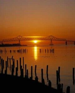 Daytrip from Portland - the sun sets in the west under the Astoria-Megler Bridge as the great Columbia river flows into the Pacific Ocean. This 4.1 mile long marvel of engineering spans the Columbia between Astoria, Oregon and  Point Ellice, Washington
