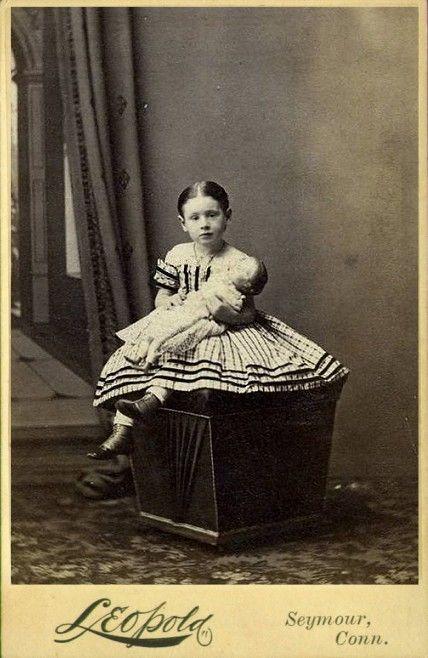 douce jeune fille AVEC Une robe à carreaux et poupée