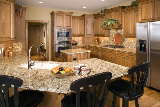 This kitchen has birch cabinets and floor, granite counter tops. Staggered cabinet heights add interest.