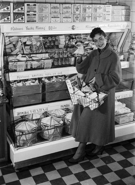 A lovely swing coat wearing lady picking up a few items at the local market during the 1950s. #woman #shopping #grocery #store #vintage #retro #supermarket