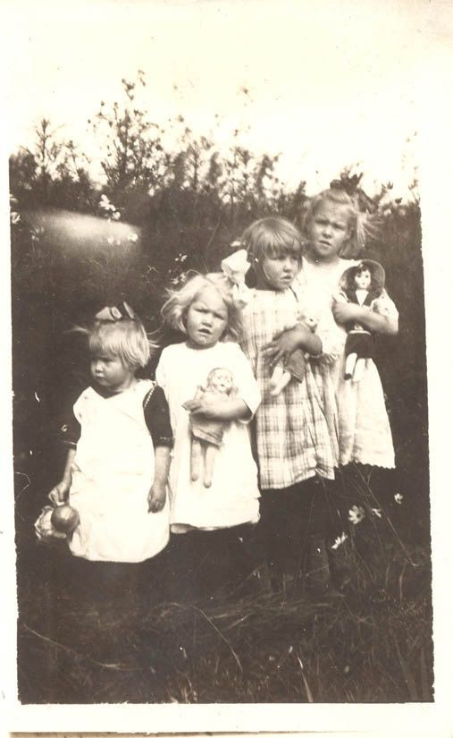 Vintage photo of four little girls and their dolls, circa 1920's.