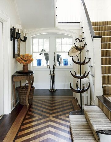 The chocolate herringbone pattern is painted on the floor and done so well it looks like inlay. The striped stair runner is  complementary to the design.   This entry looks like it could be from a Kentucky estate. Possibly it is the horse figurine that sets that