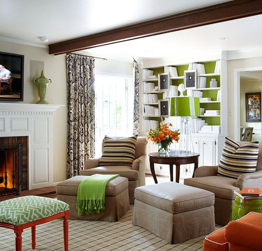 "Homeowner/designer Tobi Fairley enlarged the mantel shelf in the family room and painted it. ""I left the beams unpainted because it made the room homey."" Tobi painted the backs of bookcases green to balance the room's orange and black-and-white."