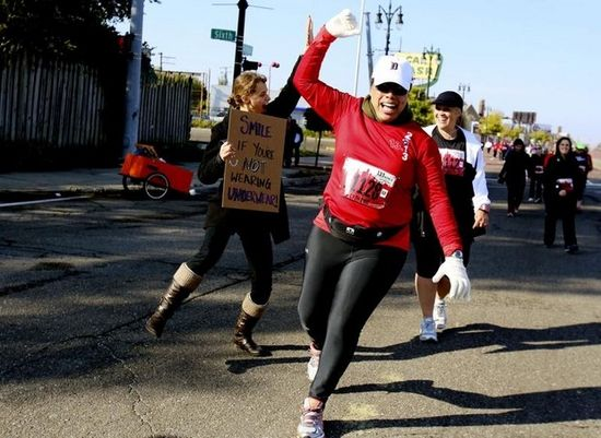 I'm Smiling ! Dannille Riley, 45, of Ann Arbor,front , gives a high-five to Corina Szabo, 24, left, of Royal Oak who holds a funny sign as she cheers on runners during the 36th annual Detroit Free Press/Talmer Bank Marathon in Detroit.