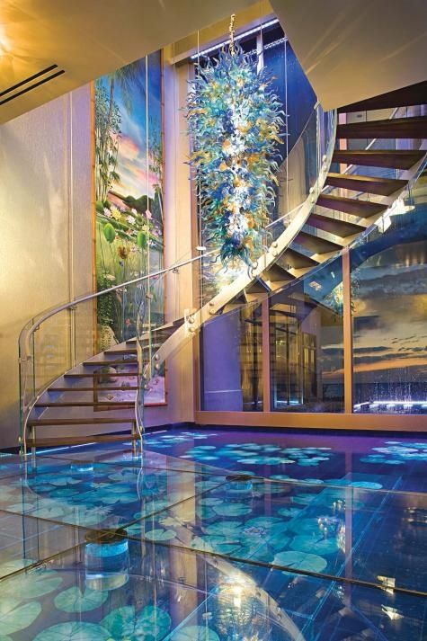 """Acqua Liana features a first ever glass """"water floor"""" with hand-painted tiles in a Monet-inspired Lotus garden motif brilliantly illuminated below the shimmering surface   2,000 gallon arched aquarium wet bar (walk below with over 100 exotic fish swimming above!)"""