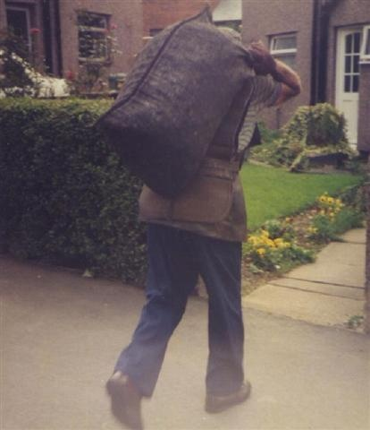 The coal man delivering a sack of coal and emptying it into the concrete coal bunker in the back garden. I used to have to,count the bags of coal,as they were being delivered