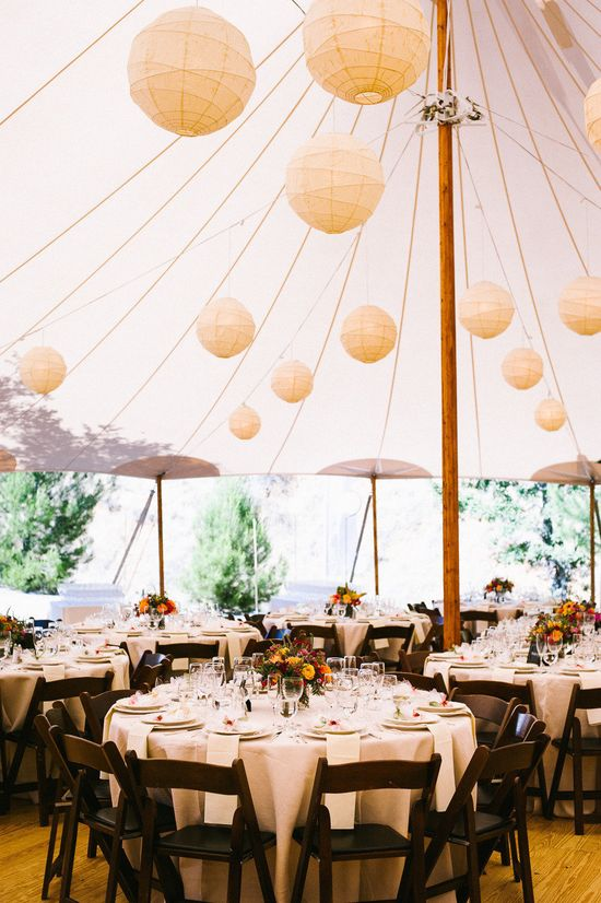 Round tables under an outdoor tent with lanterns