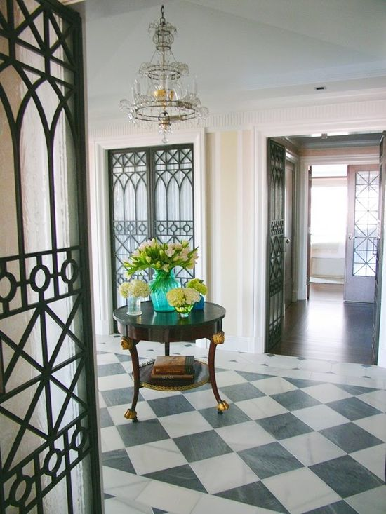 Foyer with checkered grey and off white marble floor, iron galss doors, crystal chandelier and a round table