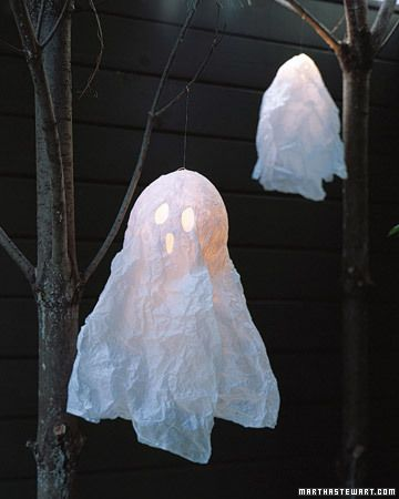 DIY Floating Ghosts by marthastewart: Tissue paper papier mache over a balloon which is popped when the paper is dry and finished with a battery power light. #Ghost #DIY #marthastewart #Halloween