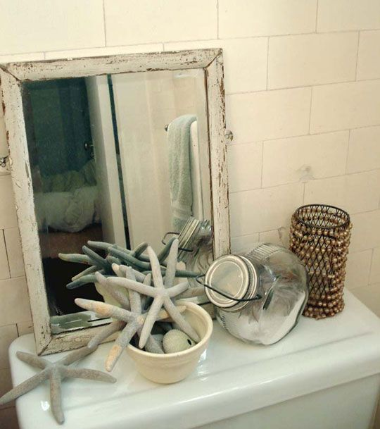 sand and a few starfish in a decorative bowl complement the mirror, thus giving the space a bigger feel.