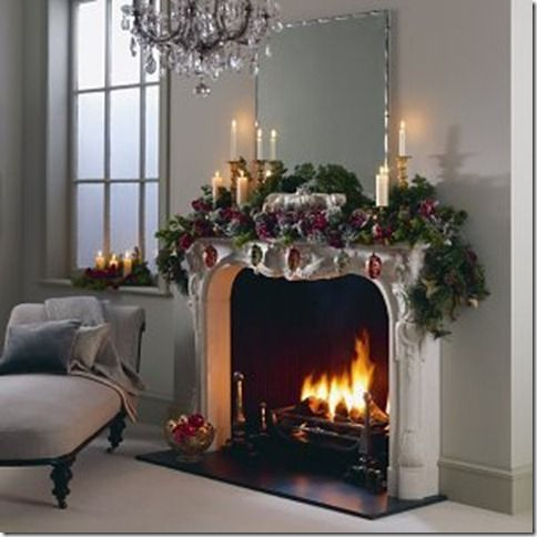 Christmas decorating with a French influence.  Beautiful mantle garland with candles of different heights worked in.