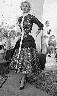 """Buyers from all parts of the world have gathered to view the fall and winter collections of Rome's leading fashion designers. One of the eye-catchers in the collection displayed by Emilio Schubert is this winter evening frock. Of black lace, it features a silk pleated wrap below the waist and ermine collar with full length narrow front. Rome, July 1954."" #vintage #fashion #1950s #designer #dress"