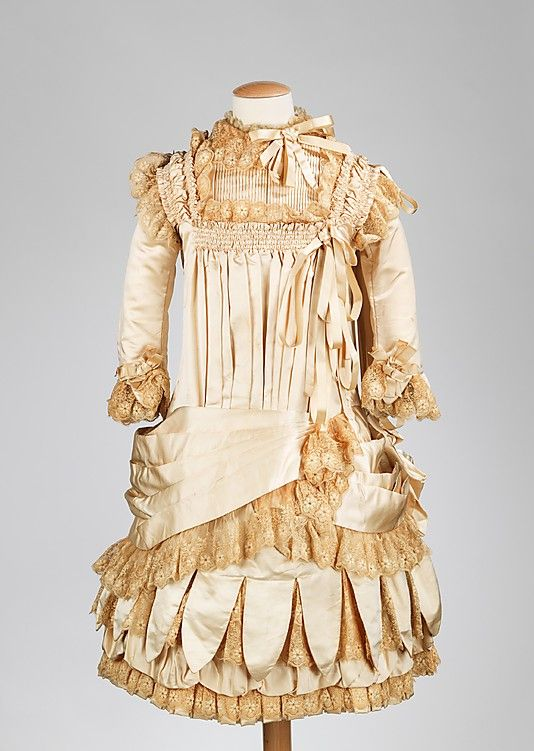 Incorporating the high-style elements and silhouette, this dress is a 'tour de force' of elaborate dressmaking of the 1880s. It was common for children's clothing to have hints of the stylish bustle of the 1880s without the full-blown aspect of the silhouette.