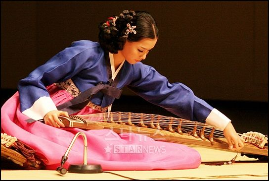 Woman in Hanbok is playing gayageum: A gayageum is a traditional Korean zither-like string instrument, with 12 strings, although more recently variants have been constructed with 21 or other numbers of strings. It draws its name from the ancient Korean confederacy of Gaya, where it is said to have been invented. It is probably the best known traditional Korean musical instrument.