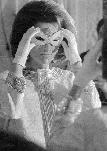 Lee Radziwill putting on her amsk for truman Capote's Black and White Dance, November 1966.