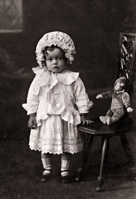 antique photo of little girl with her toy monkey