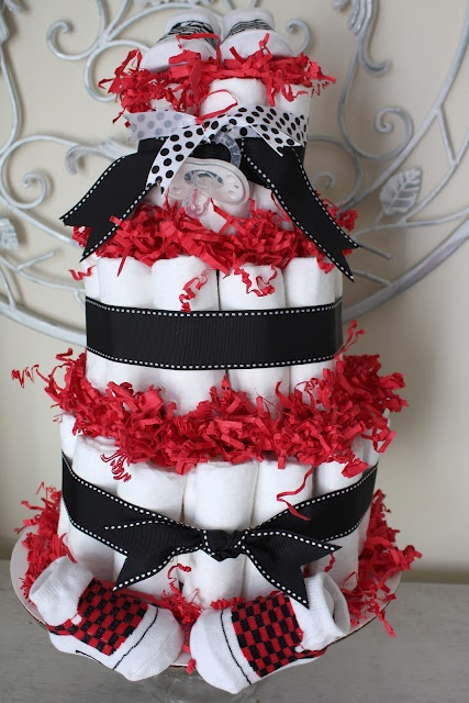 Diaper cake for a boy with bag filler materials topping rolled diapers, surrounded by ribbon and at the very top, a pair of checkered black and white socks.