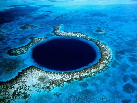 The Great Blue Hole, a World Heritage site,  is a large underwater sinkhole off the coast of Belize. Jacques Cousteau took the Calypso and his one-man submarines into the hole in 1972 to examine stalactites suspended from overhanging walls. The Great Blue Hole is surrounded by shallow water of Lighthouse Reef Atoll, a nearly perfect circle in the middle of a shallow reef.