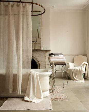 Gorgeous Bathroom. Love the tub & oval shaped shower curtain. Love the fireplace, etc.