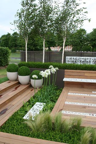 Contemporary Contemplation Garden at the RHS Hampton Court Flower Show in the UK by garden designer One Abode Ltd. This contemporary and stylish garden features structural planting with a graphic formation of spectacular white flowering Agapanthus.