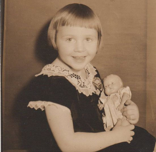 Happy girl with her doll; 1950's.