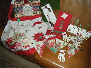 SANTA....  S=scarf  A=Assorted Chocolates  N=Nostalgic graphics Banner  T=Tea Towels  A=Apron