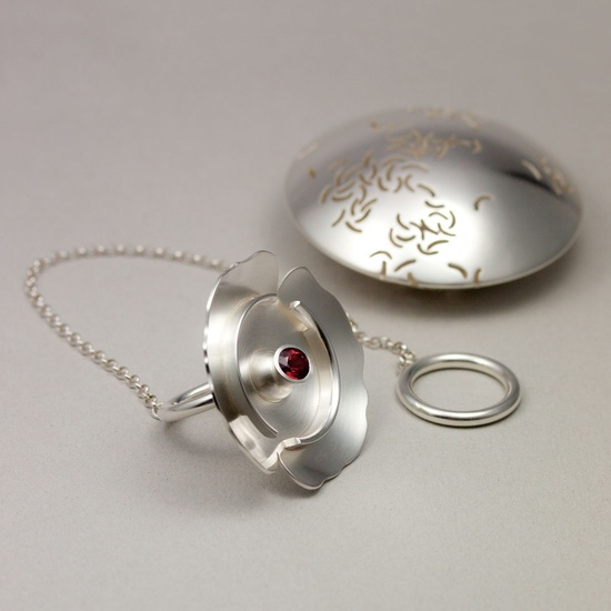 Tekula/ring. Silver och granat. - Tea ball/ring in silver, open to show the beautiful teared  garnet inside!