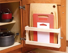 Magazine rack on cabinet door to store cutting boards.