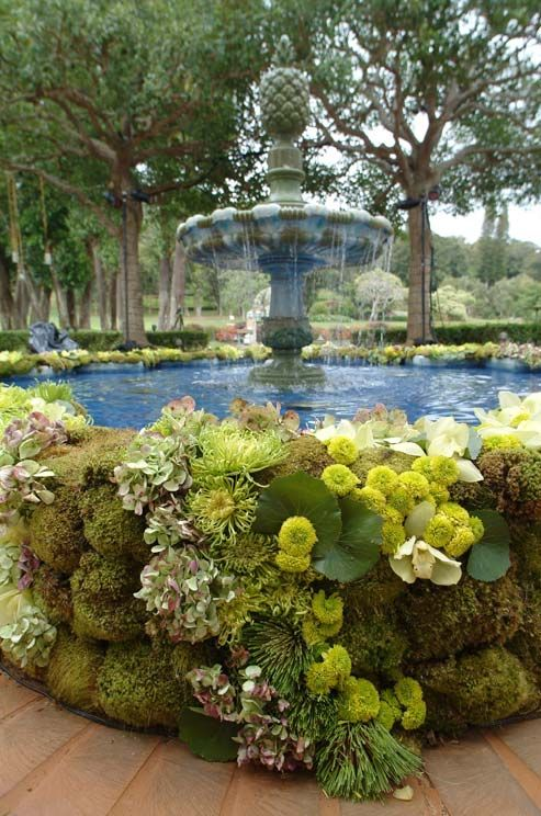 Bundles of moss, pink and green hydrangeas, pincushion proteas and   white orchids add a natural touch to this beautiful fountain.