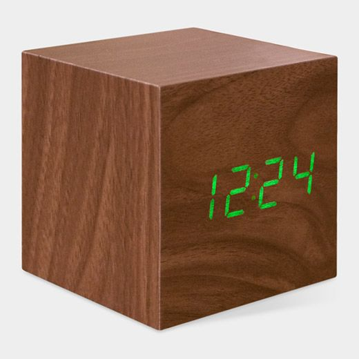 Cube Clock from MoMA! :) Sound activated -- just snap your fingers or tap the top of this cube and the green LED display illuminates to reveal the time, date, and temperature. After a few seconds, it will automatically turn off. Made of WOOD with plastic wood-grain walnut veneer. !