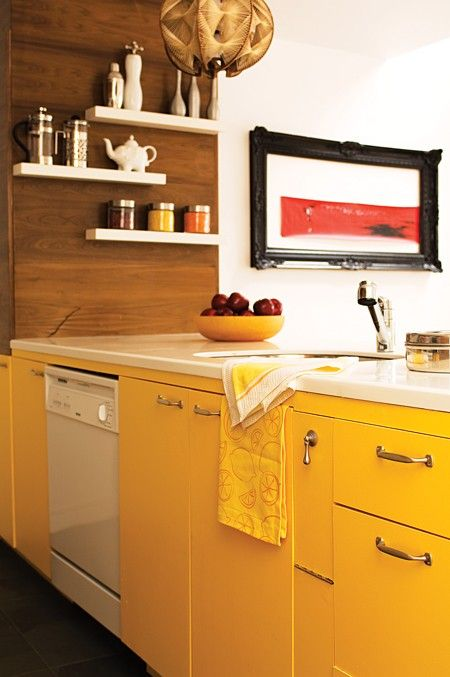 An orangey-yellow paint covers this kitchen's lower cabinets. In a subtler turn, upper and outer cabinets are treated to a rich walnut veneer. Yellow dish towels and accessories keep the look saturated.