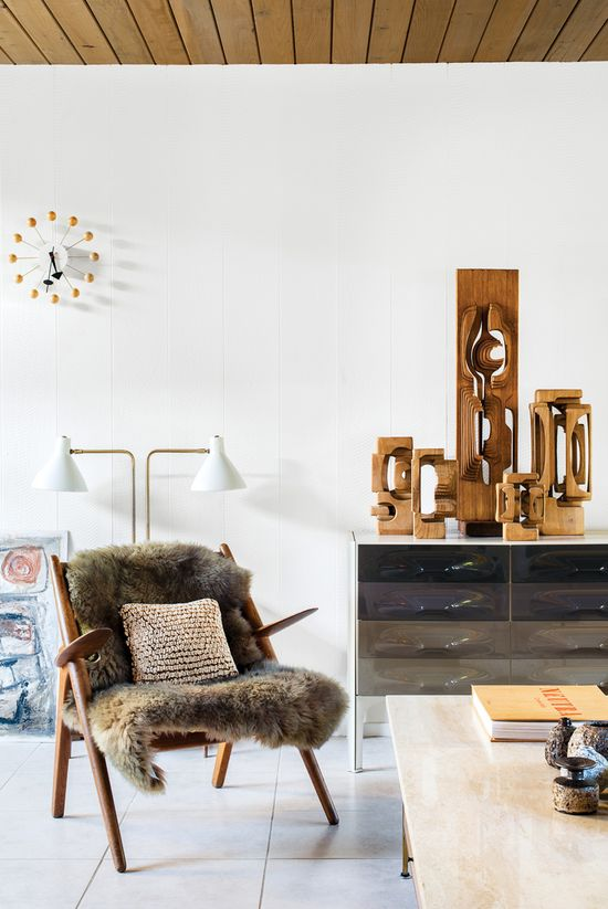 Mark Neely and Paul Kefalides's living room is decked out with the couple's vintage finds, including a Hans Wegner Sawback chair (the fur throw obscures an area needing repair), a George Nelson Ball Clock, a DF-2000 cabinet by Raymond Loewy, a light designed by Greta Von Nessen, and a suite of Brian Willshire wooden sculptures, one of Neely's many collections. Photo by: Drew Kelly