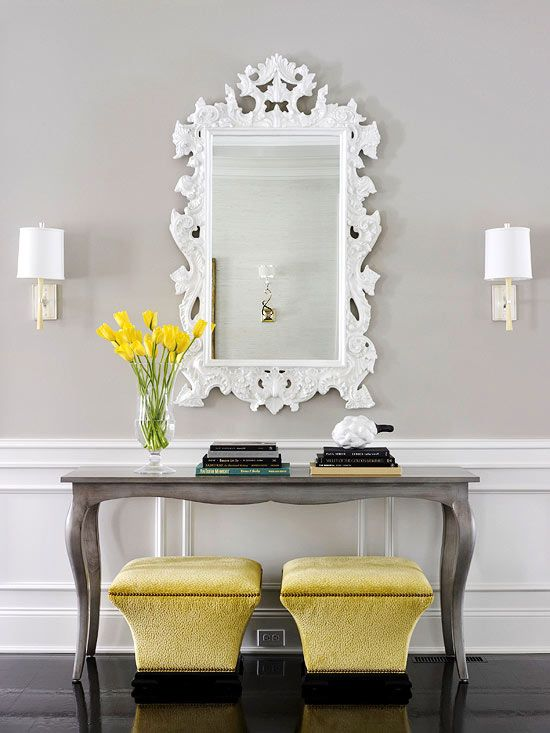 Traditional neutral gray entryway with white panel wainscoting. Gorgeous plush, slightly modern ottomans upholstered in a citron yellow velvet. Console table has an edgy vibe with a zinc painted finish. I would love to look at myself everyday in that  fabulous intricate filigree white mirror.