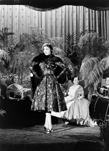 A model sporting a wonderfully pretty floral print dress and fur cape for an audience. #vintage #fashion #1950s