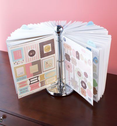 A paper towel holder with page protectors attached by rings.Could be a way to store recipes, photos, cards, etc.